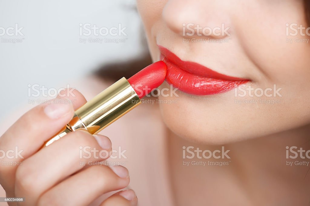 Cheerful young girl is doing her make-up stock photo