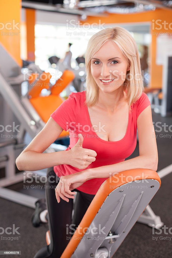 Cheerful young girl is training in fitness center stock photo