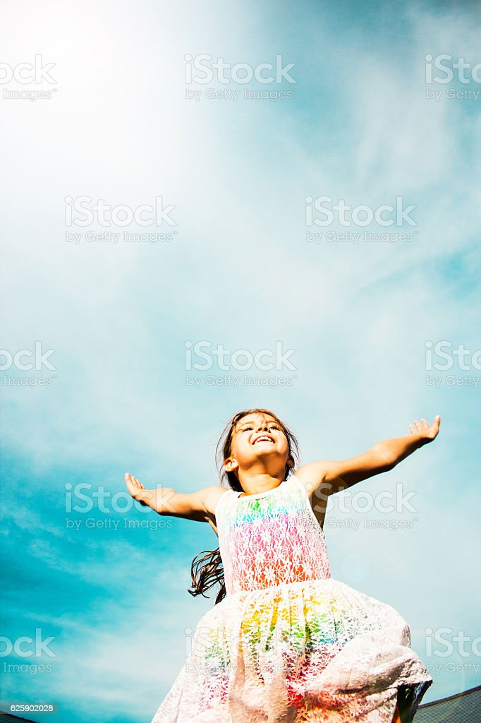 cheerful young girl jumping on trampoline royalty-free stock photo