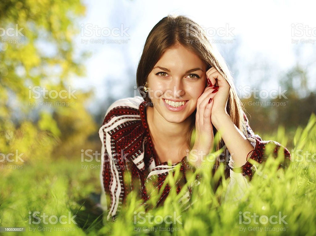 Cheerful young girl lying on green grass royalty-free stock photo