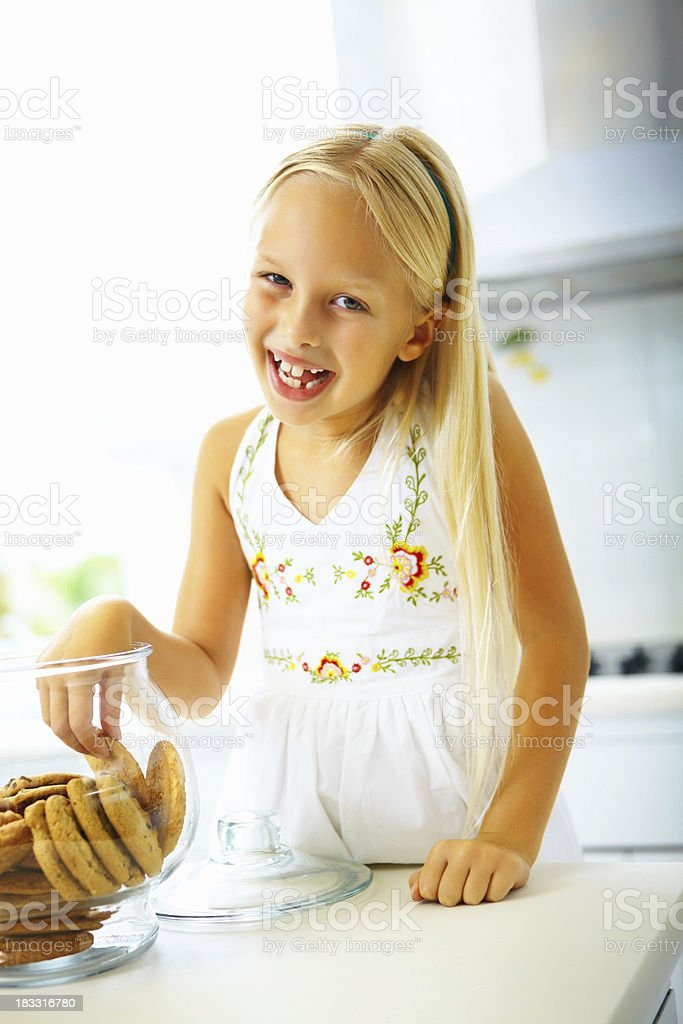 Cheerful young girl taking cookies from a cookie jar royalty-free stock photo