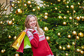 Cheerful young girl with colorful shopping bags