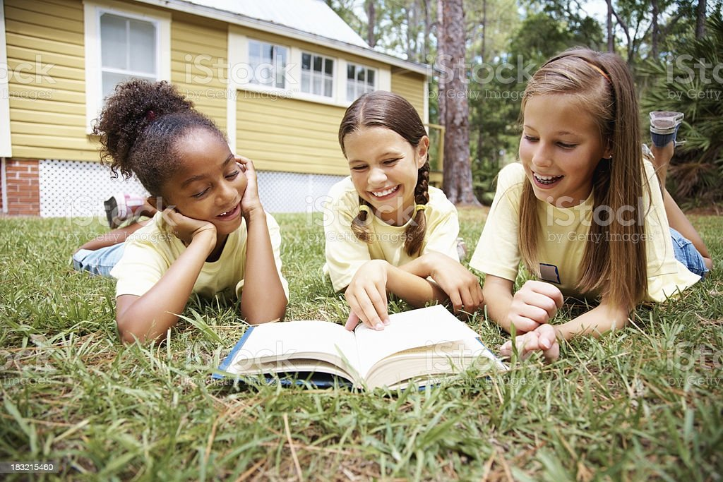 Cheerful young girls reading book while lying in a lawn royalty-free stock photo