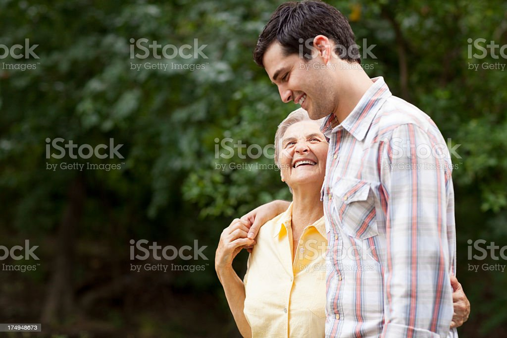 Cheerful young grandson and grandma walking royalty-free stock photo