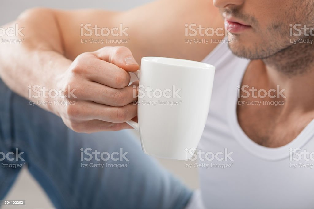 Cheerful young guy is drinking hot tea stock photo