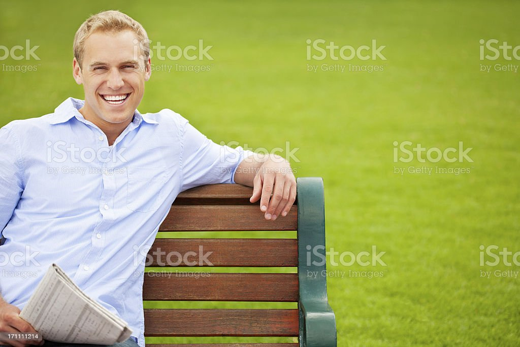Cheerful Young Guy Sitting On a Park Bench royalty-free stock photo