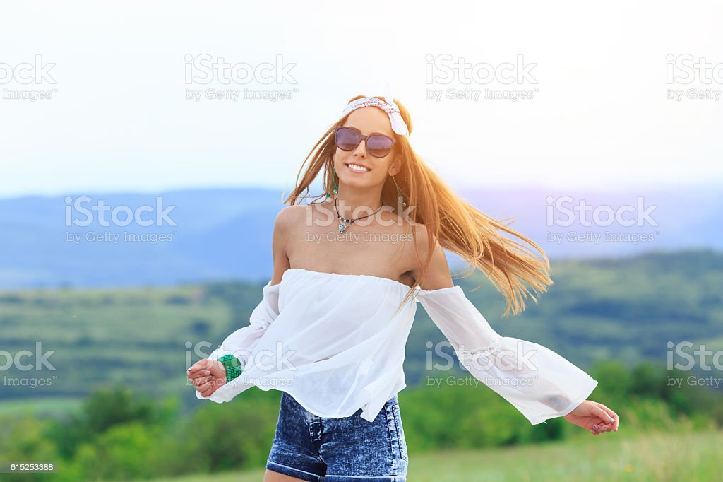 Cheerful young hippie woman dancing on country road stock photo