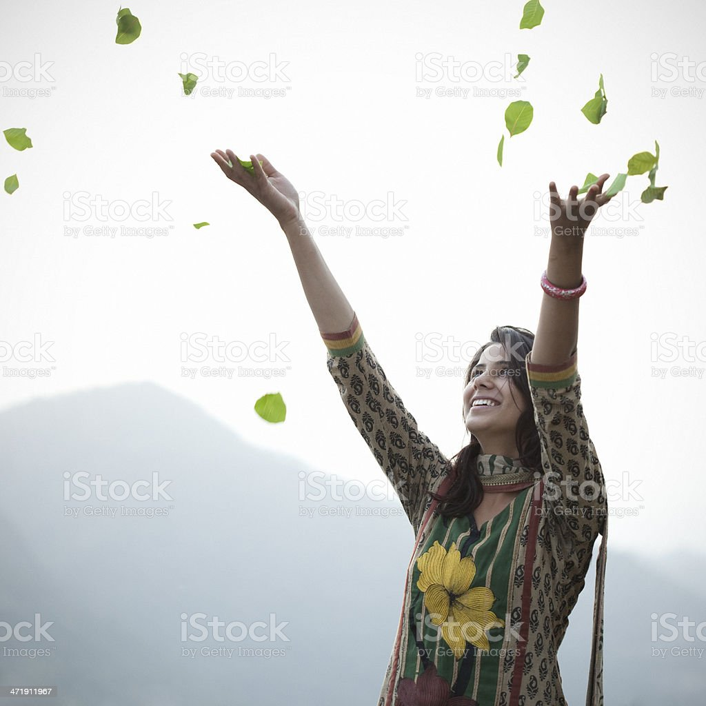 Cheerful, young Indian woman throwing leaves up in air stock photo