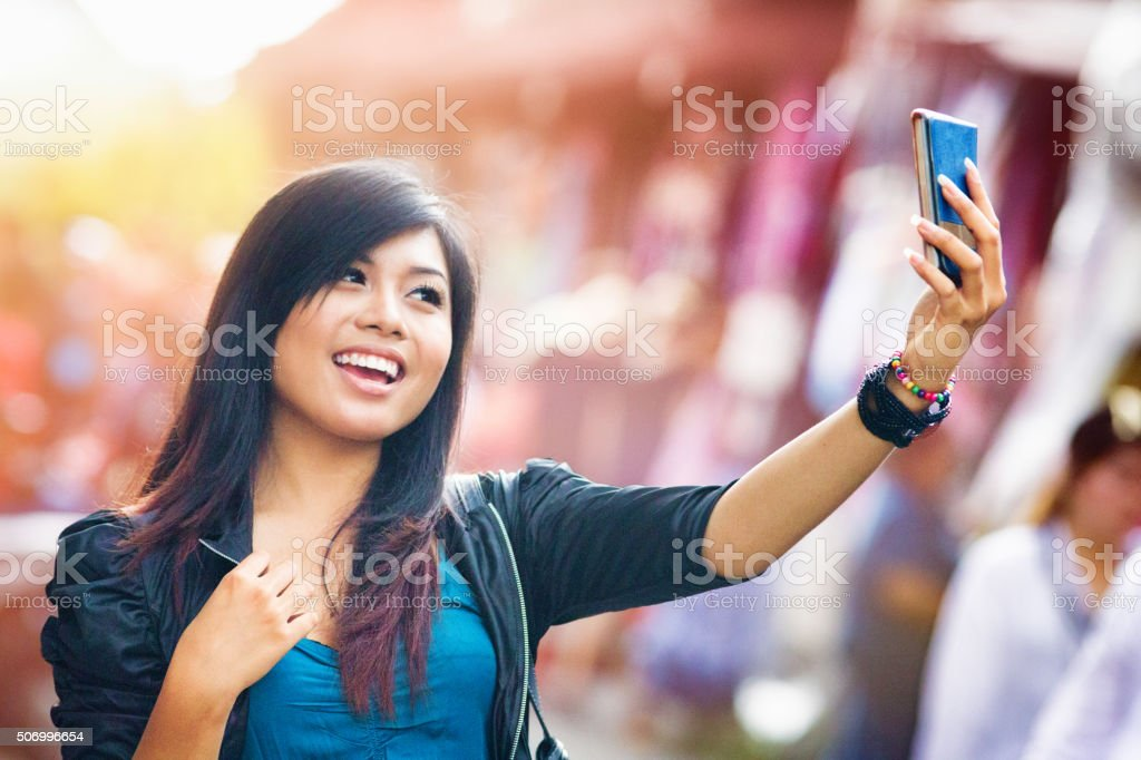 Cheerful Young Indonesian female shooting a selfie stock photo