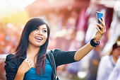 Cheerful Young Indonesian female shooting a selfie