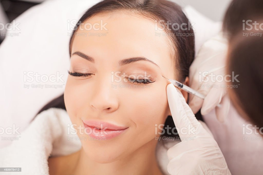 Cheerful young lady is having procedure at clinic stock photo