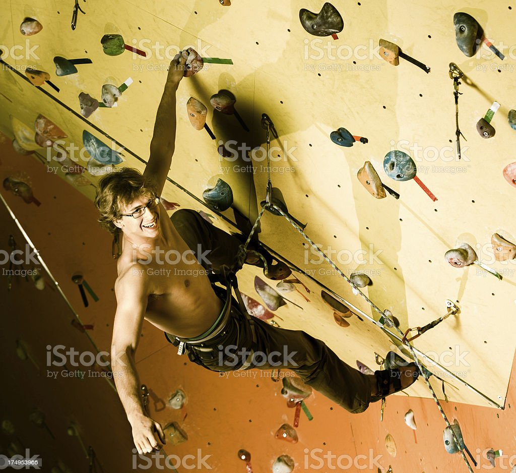 Cheerful young man climbing an artificial rock royalty-free stock photo