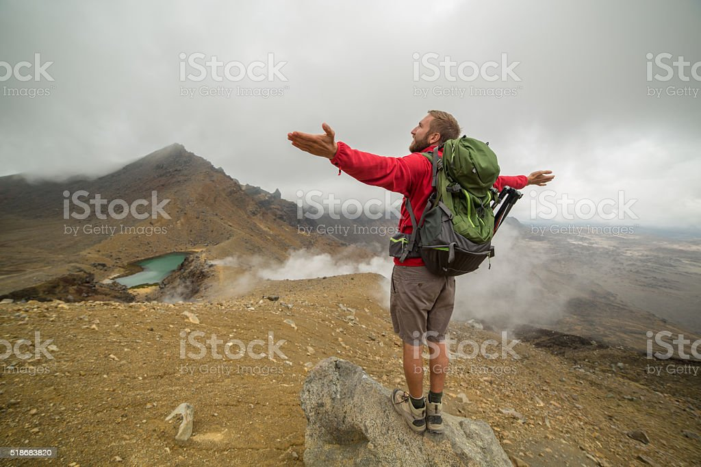 Cheerful young man hiking on Tongariro Alpine Crossing stretches arms stock photo