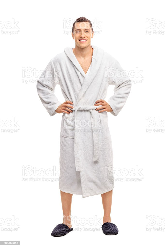 Cheerful young man in a white bathrobe stock photo