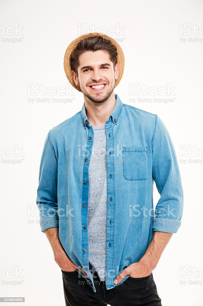 Cheerful young man in hat standing with hands in pockets stock photo