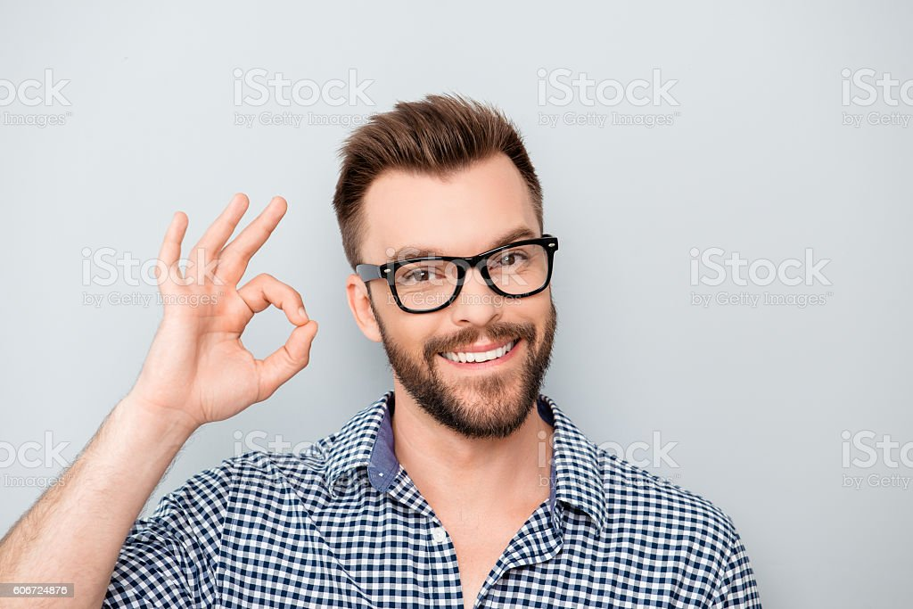 Cheerful young man in spectacles showing 'OK' gesture stock photo