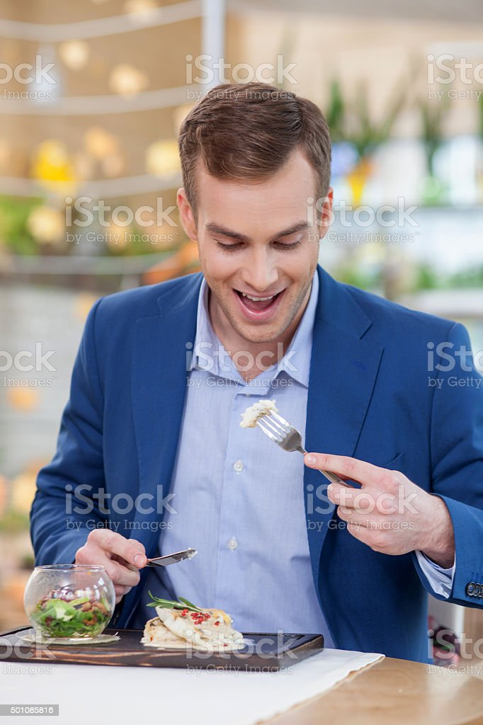 Cheerful young man is tasting food at restaurant stock photo