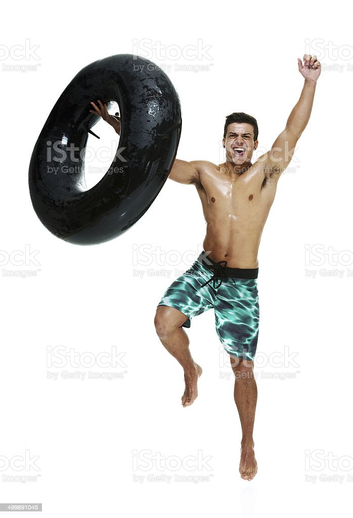 Cheerful young man jumping with inner tube royalty-free stock photo