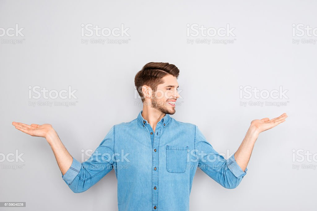 Cheerful young man presenting products in both hands stock photo
