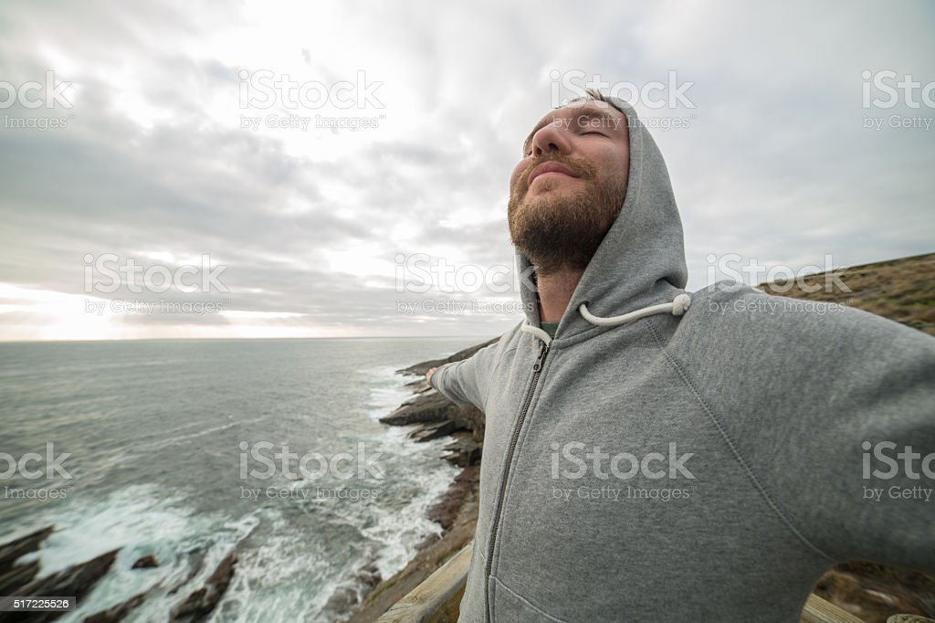 Cheerful young man relaxes by the sea stock photo
