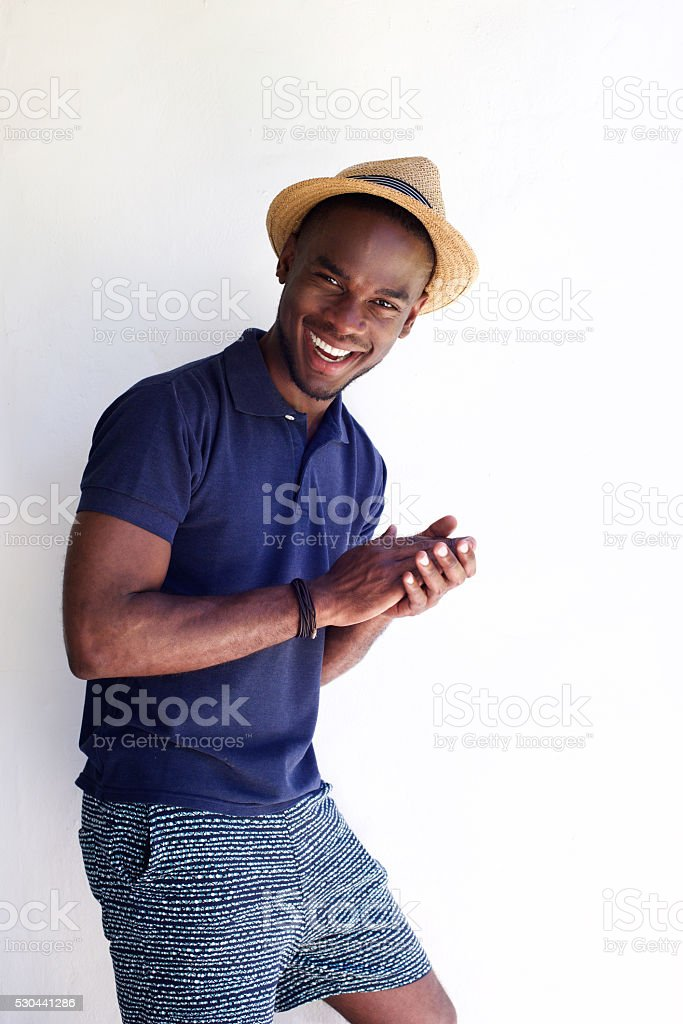 Cheerful young man standing against white background stock photo