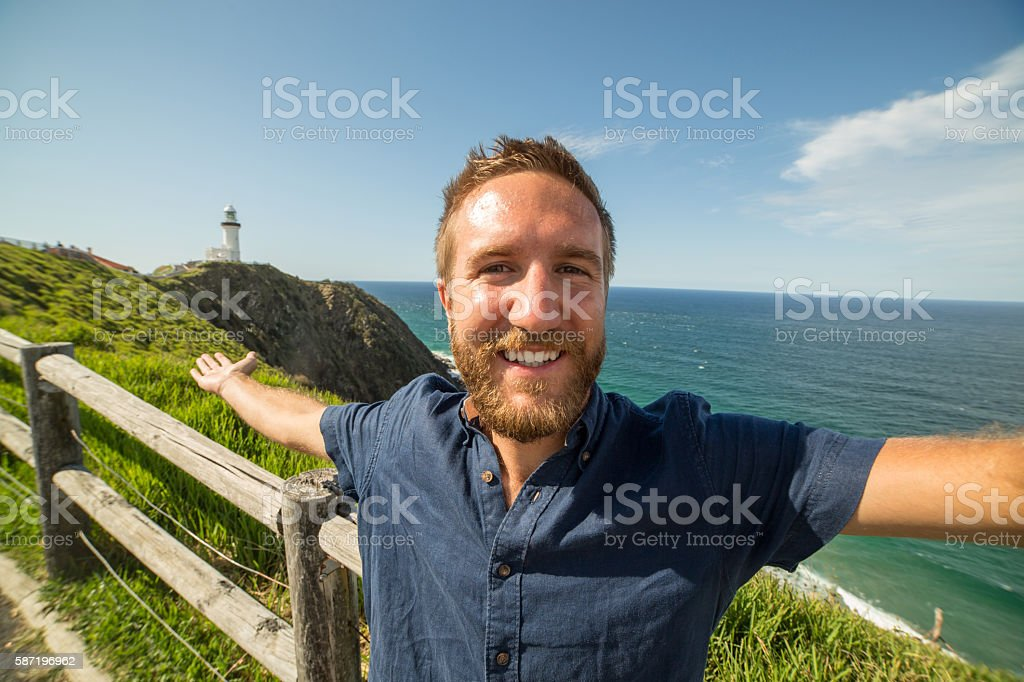 Cheerful young man takes a selfie portrait at Cape Byron stock photo