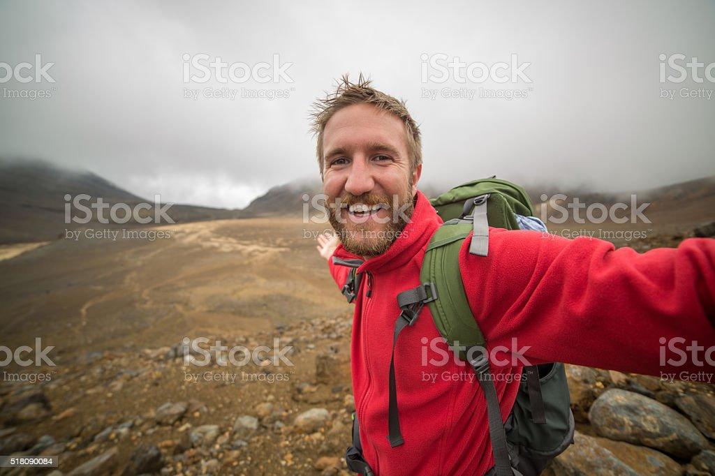 Cheerful young man takes selfie portrait on Tongariro Alpine Crossing stock photo