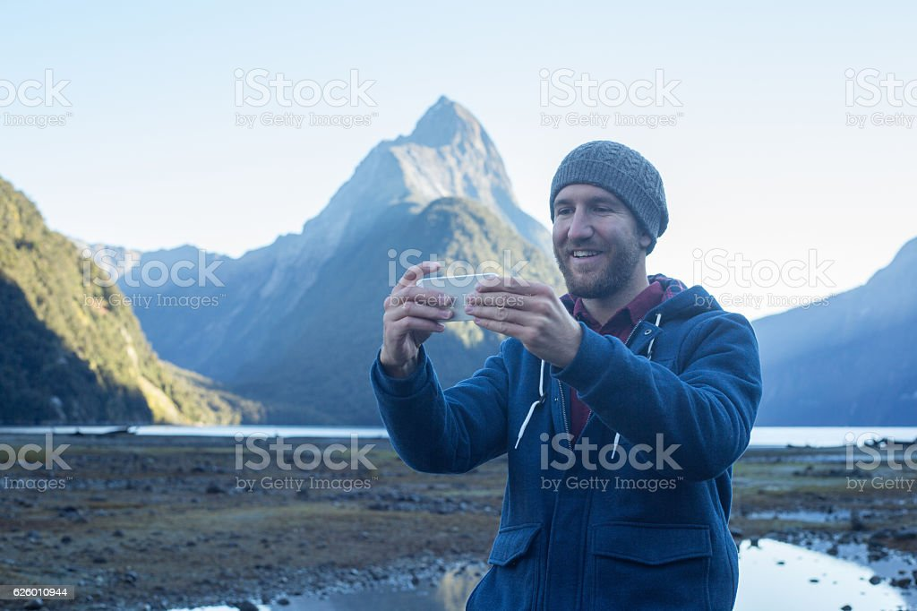 Cheerful young man takes selfie portrait using smart phone stock photo