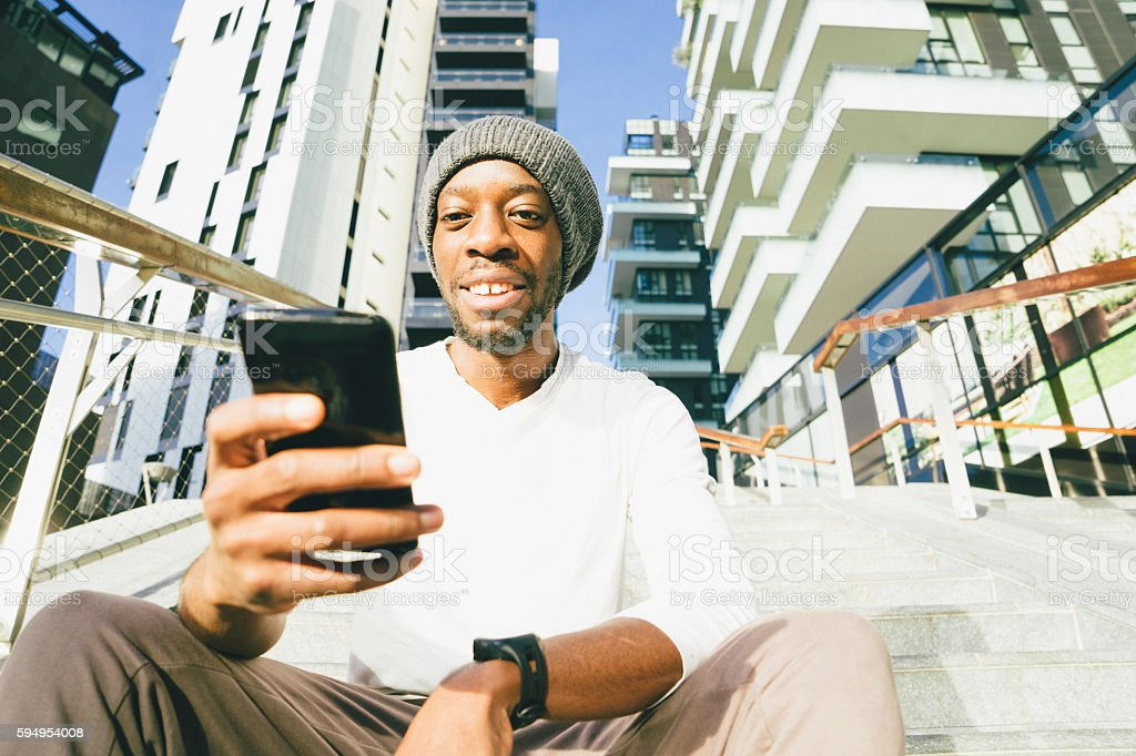 Cheerful Young Man Using His Smartwatch And Smartphone stock photo