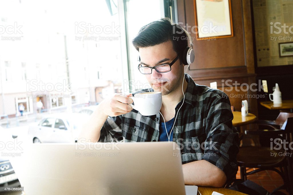 Cheerful Young Man Using Laptop In Coffee Shop stock photo