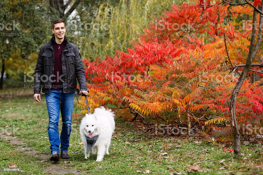 Cheerful young man taking a walk with her dog in the park. Front...