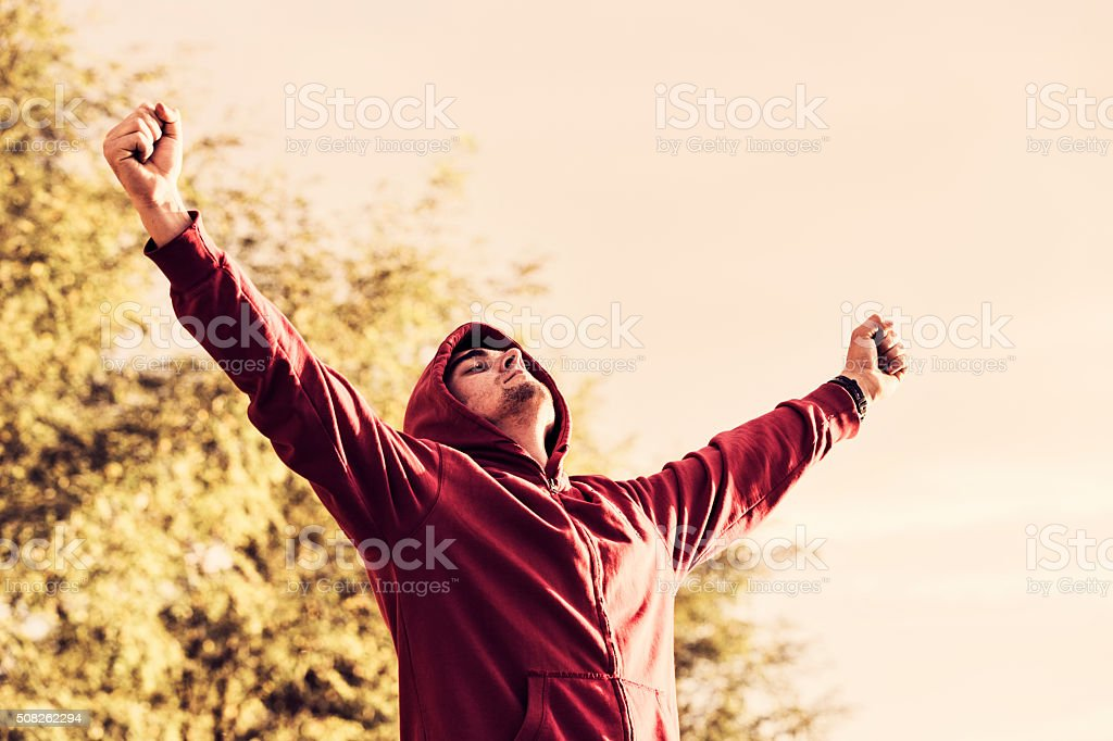 Cheerful young man with arms spread open outdoors stock photo