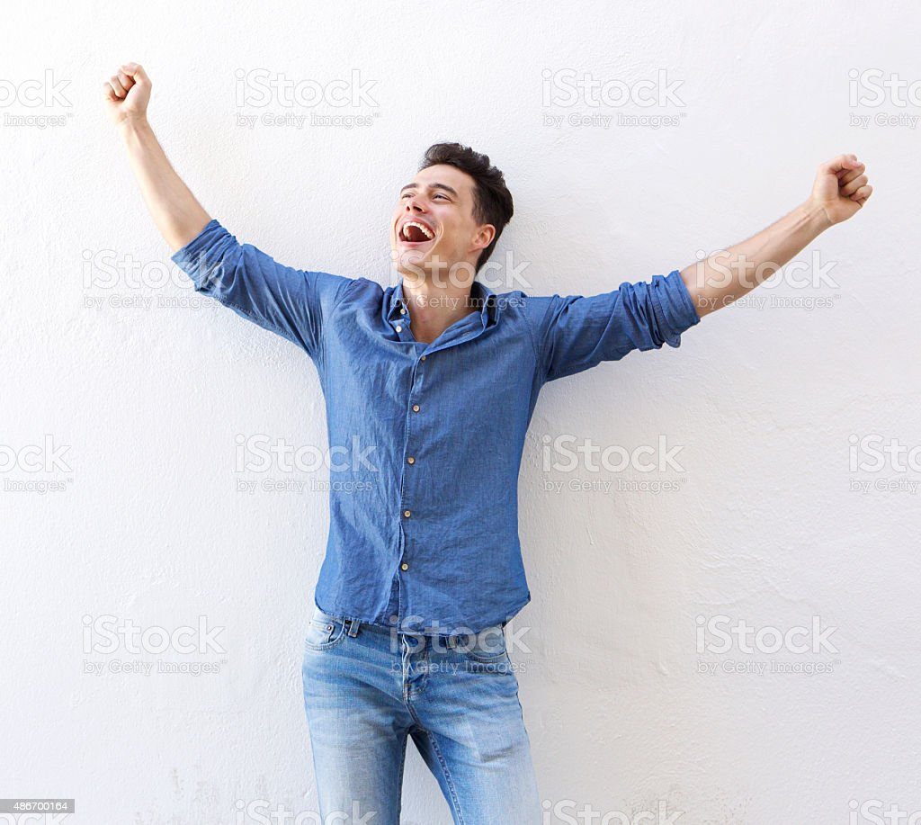 Cheerful young man with raised arms celebrating stock photo