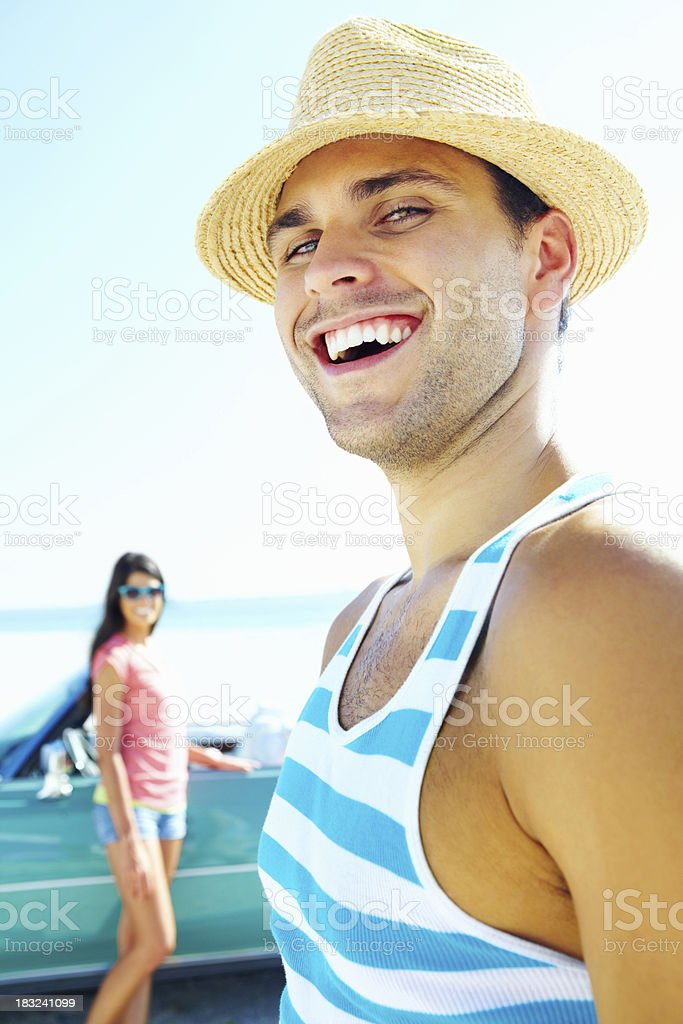 Cheerful young man with woman and car in background royalty-free stock photo