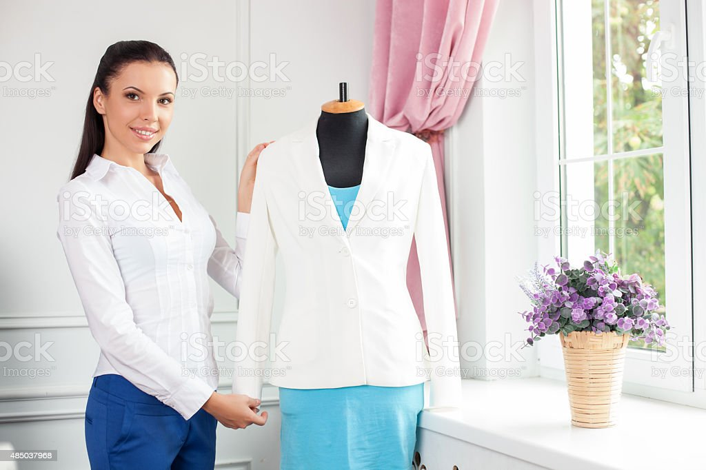 Cheerful young modern tailor is creating new costume stock photo