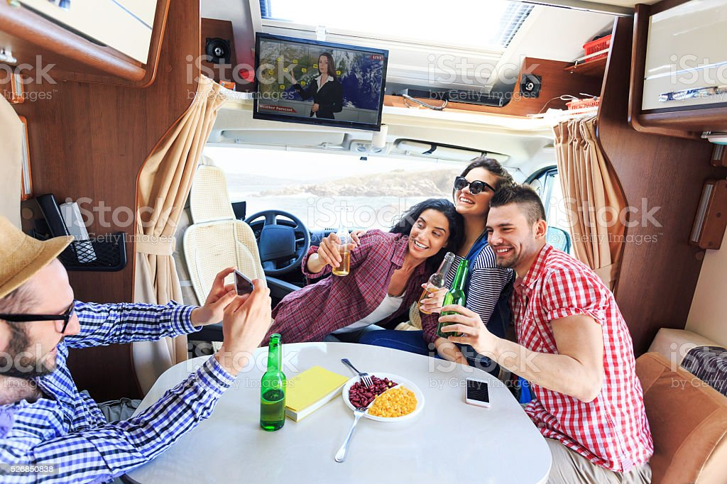 Cheerful young people having fun inside of a camper stock photo