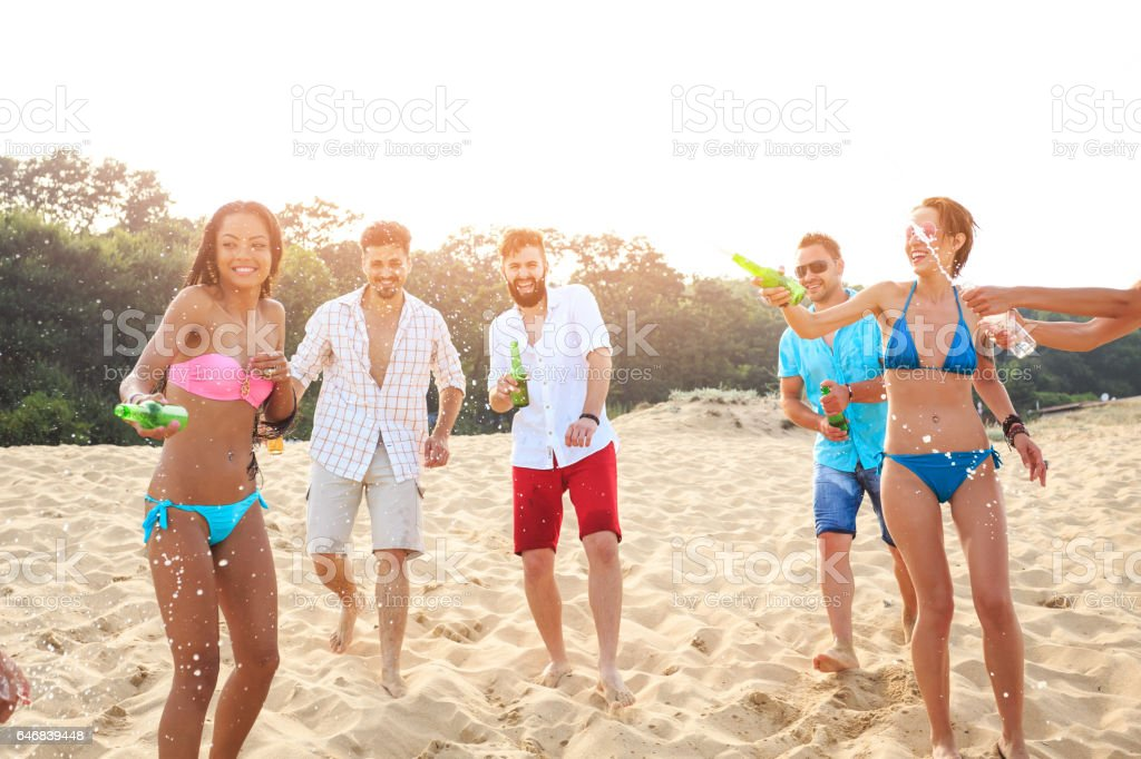 Cheerful young people having fun together on sand stock photo