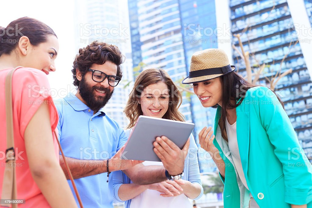 Cheerful young people in the city with digital tablet. stock photo