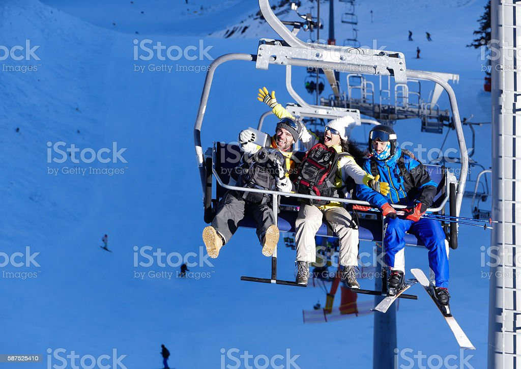 Cheerful young people making selfie on ski lift stock photo