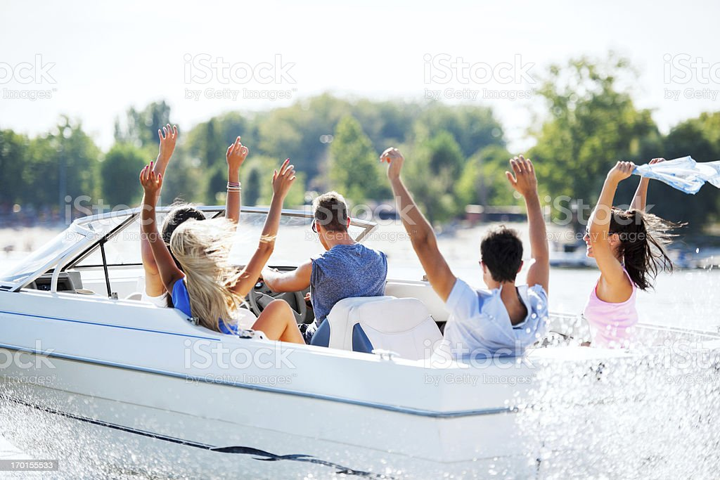 Cheerful young people riding in a speedboat stock photo