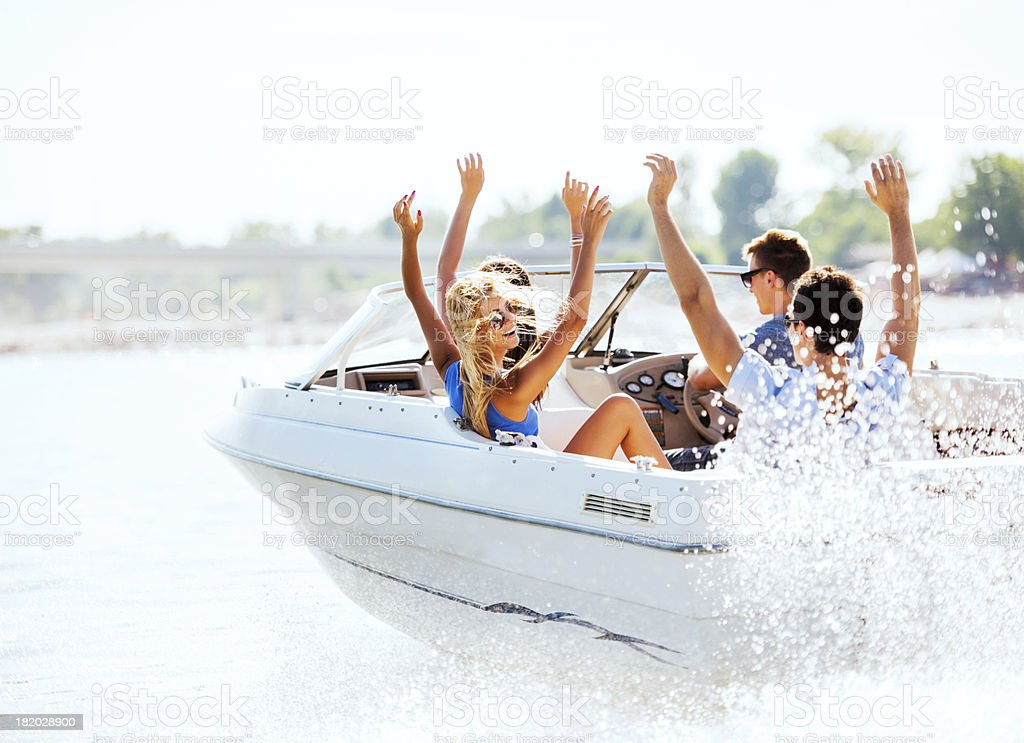 Cheerful young people riding in a speedboat. stock photo