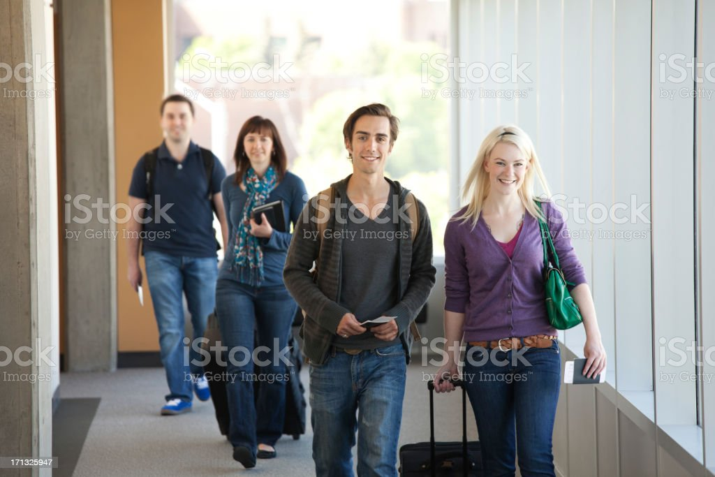 Cheerful young people travelling in airport corridor. royalty-free stock photo