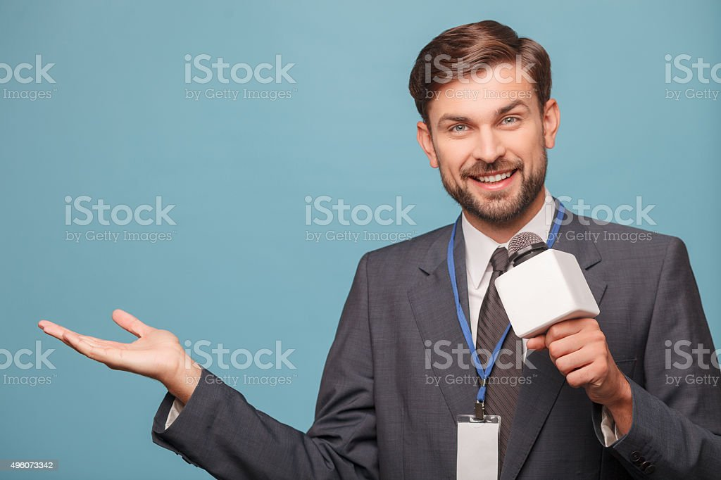 Cheerful young reporter is working with joy stock photo