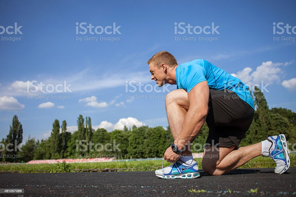Cheerful young sportsman is preparing before running stock photo