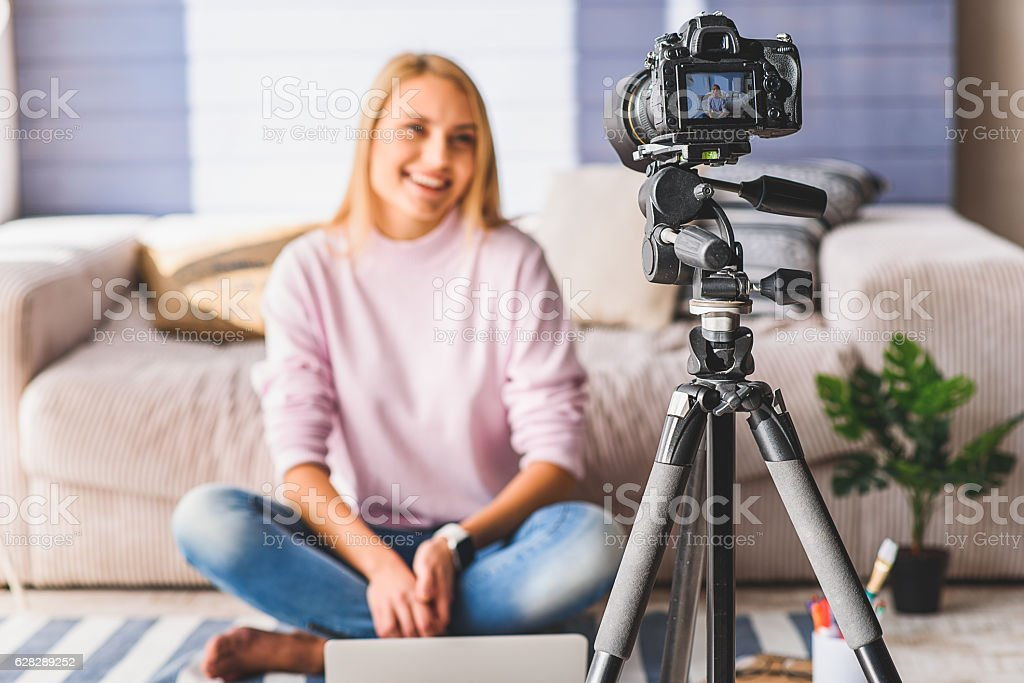 Cheerful young woman blogging at home stock photo