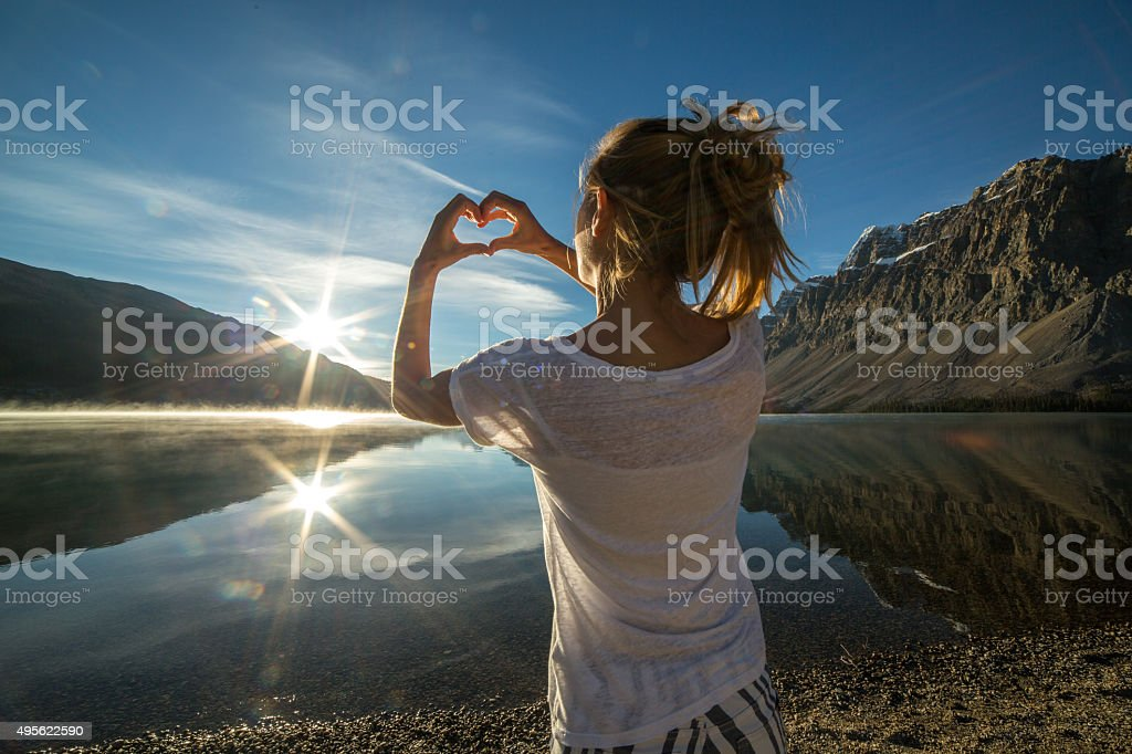 Cheerful young woman by the lake loving nature stock photo