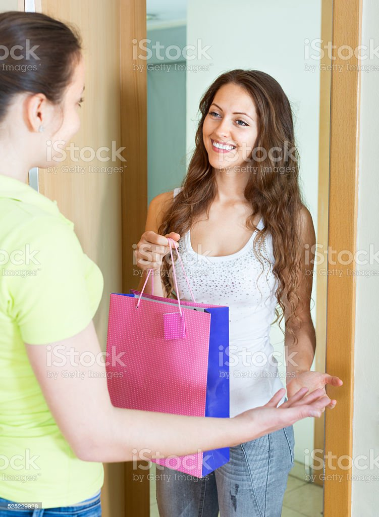 Cheerful young woman congratulating her friend stock photo