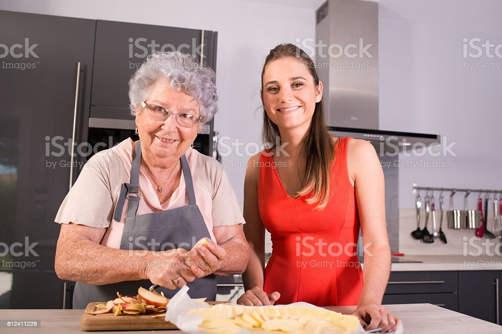cheerful young woman cooking apple pie together with elderly grandmother stock photo