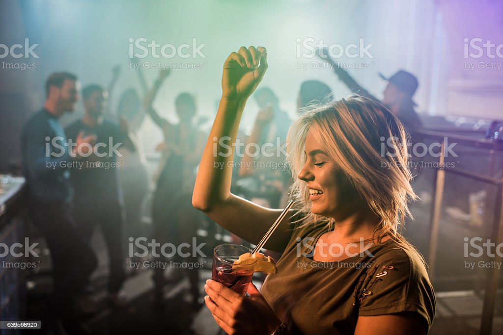 Cheerful young woman dancing during the party in nightclub. stock photo