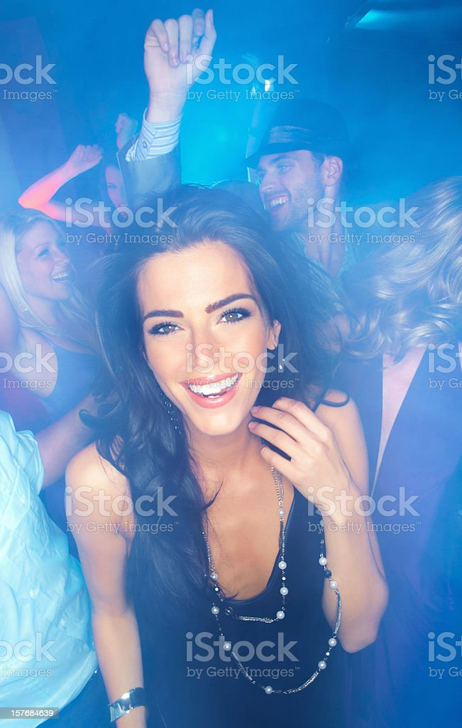 Cheerful young woman dancing with her friends at a disco stock photo